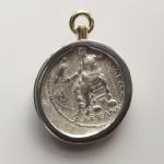 "Alexander the Great Swivel Pendant: Silver tetradrachm 336-323 BC set in 18 kt. gold bezel and swivel; (reverse view) Zeus sitting, legs side by side, holding an eagle and scepter; ""of Alexander"" in Greek letters."