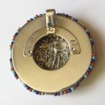 King Azes Pendant: Silver tetradrachm 50 BC-5 AD set in blue enamel and 18 kt. gold bezel embellished with 18 kt. gold hand-braided wire, and coral, turquoise, and lapis beads; (reverse view) Pallas Athena.