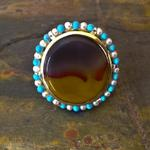 Ceremonial Ring I: (Top view) Kentucky Agate 18mm x 20mm set in an 18 kt. yellow gold bezel in sterling silver; Eighteen 3mm pearls and eighteen 3mm turquoise strung on silver wire around the bezel; Two yellow and two orange Chatham sapphires; Ring size 9.