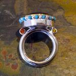 Ceremonial Ring I: (Front view) Kentucky Agate 18mm x 20mm set in an 18 kt. yellow gold bezel in sterling silver; Eighteen 3mm pearls and eighteen 3mm turquoise strung on silver wire around the bezel; Two yellow and two orange Chatham sapphires; Ring size 9.