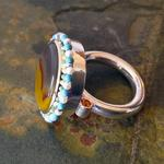 Ceremonial Ring I: (Side view) Kentucky Agate 18mm x 20mm set in an 18 kt. yellow gold bezel in sterling silver; Eighteen 3mm pearls and eighteen 3mm turquoise strung on silver wire around the bezel; Two yellow and two orange Chatham sapphires; Ring size 9.