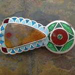 "Belt Buckle I: Champleve enamel on silver with silver and gold leaf; designed, laid out, and pierced by hand; Kentucky agate, African red jasper, and green tourmaline, set in handcrafted, riveted silver bezels; 3.5"" x 1.75"" x 3 mm."