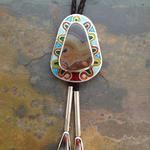 "Bolo Tie I: Champleve enamel on silver with silver and gold leaf; designed, laid out, and pierced by hand; Kentucky agates on bolo and tassels, set in handmade and riveted silver bezels; 2.25"" x 1.75"" x 3 mm. Handcrafted display box is included."